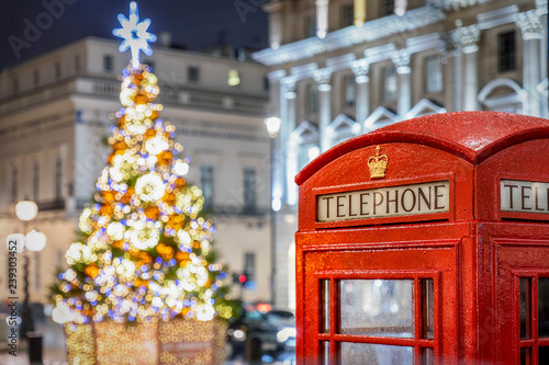 Rote Telefonzelle vor beleuchtetem Weihnachtsbaum in London zur Weihnachtszeit