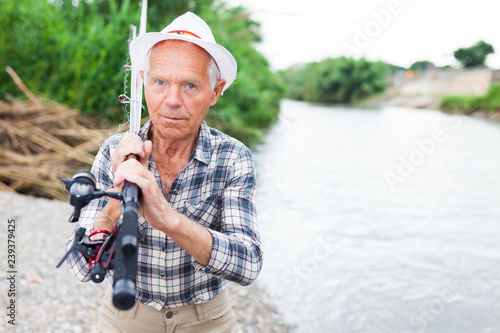 Mature fisherman with rod at riverside Fototapeta