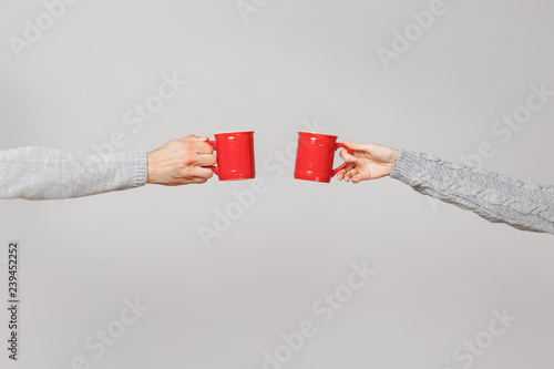 Canvas Print Close up cropped of woman, man two hands horizontal holding red cups of tea, clinking isolated on grey wall background