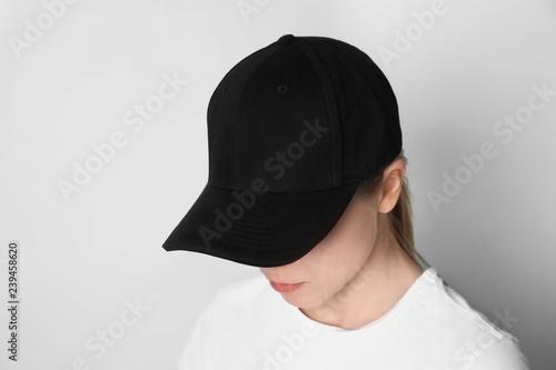 Fototapeta Woman wearing blank cap on light background
