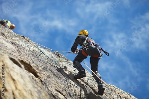 Climber climbs on the rock wall against a blue sky. Climbing gear. Climbing equipment.