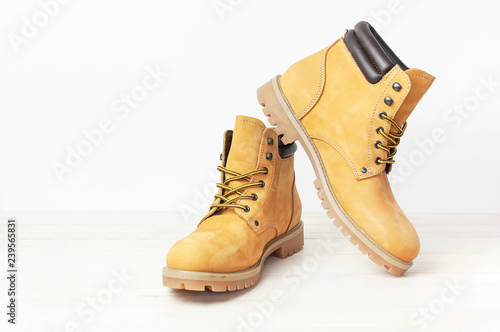 Yellow men's work boots from natural nubuck leather on wooden white background Fototapet
