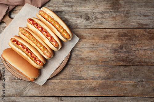 Fototapeta Tasty fresh hot dogs on wooden table, top view. Space for text