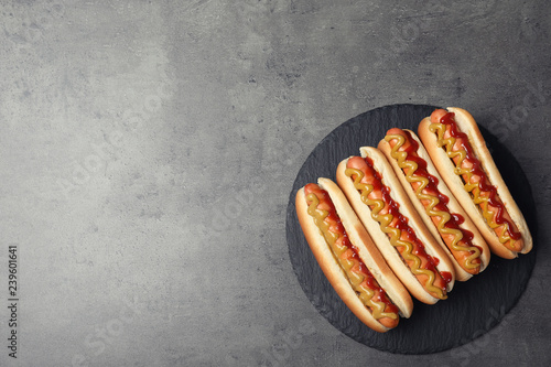 Fotografie, Obraz Slate plate with hot dogs on grey background, top view