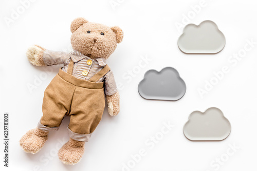 Baby care with craft toys for newborn. Teddy bear. White background top view