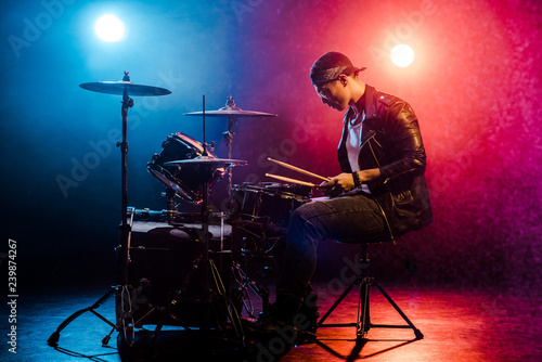 side view of male musician in leather jacket playing drums during rock concert o Fototapet