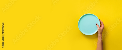 Fotografie, Obraz Female hand holding empty blue plate on yellow background with copy space