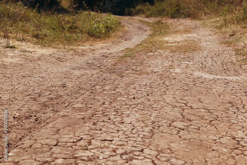Fotografiet The dry road in cracks in rural areas with droughty climate
