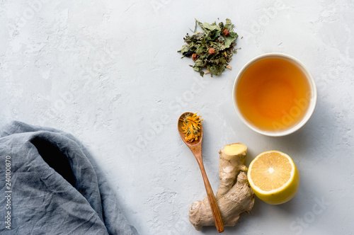Herbal tea for colds and flu. Lemon, ginger and herbs on concrete background with copy space.