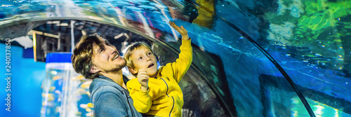 Father and son look at the fish in the aquarium in oceanarium BANNER, LONG FORMAT