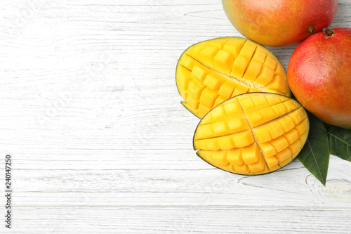 Flat lay composition with mango on white wooden background. Space for text