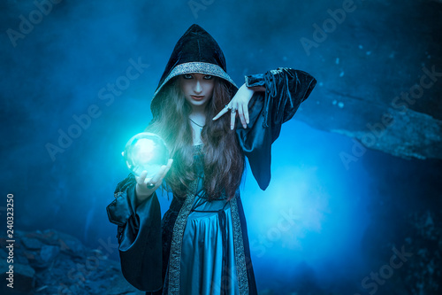 Fotografia The witch with magic ball in her hands causes a spirits