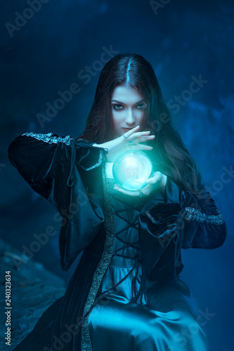 The witch with magic ball in her hands causes a spirits Fototapeta