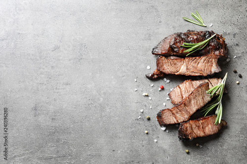 Flat lay composition with delicious barbecued meat on gray background. Space for text