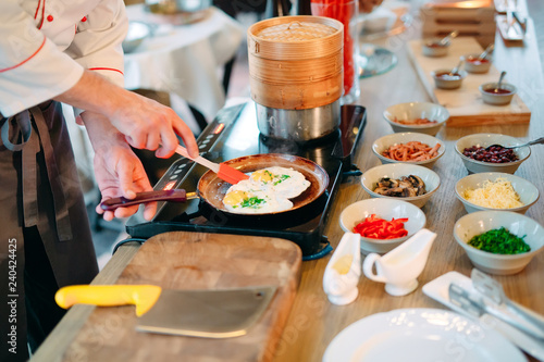 Breakfast. Scrambled eggs are cooked on an induction cooker in the restaurant.