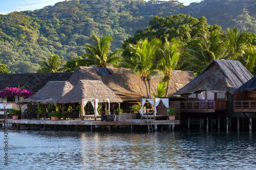 Photo Luxury overwater thatched roof bungalow resort on a wooden pontoon in the clear blue lagoon on Bora Bora in French Polynesia
