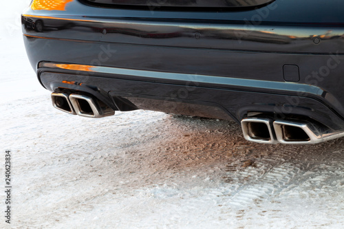 Close-up of a black luxury car bumper of a Mercedes Benz brand sedan VIP class with turbo exhaust pipes outdoors in the winter on the snow фототапет