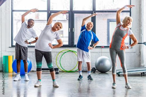 Fotografía happy multiethnic senior sportspeople synchronous exercising at sports hall