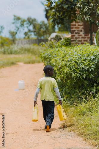 Fototapeta Boy fetching water in Uganda, Africa