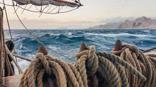 Old sailing ship running on the sea near the rocks. Belaying pin on which the ropes