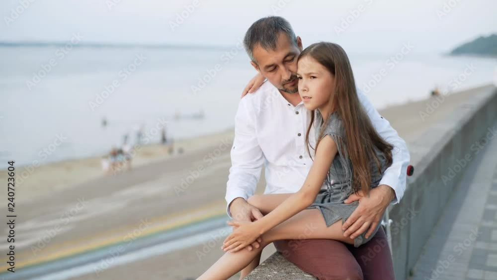 A girl sits on her father(父)'s lap. A man and his daughter(娘) are sitting on the embankment. Sunset. 4k Stock ビデオ | Adobe Stock
