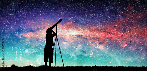 Silhouette of little child looking through a telescope