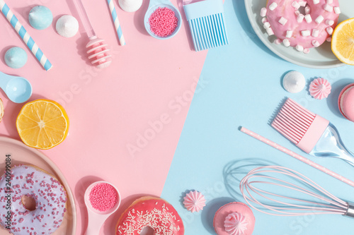 Kitchen utensils and tools, pastries and sweets on a pink and blue background. Top view. Copy space.