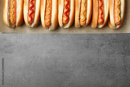 Tasty fresh hot dogs on grey background, top view. Space for text