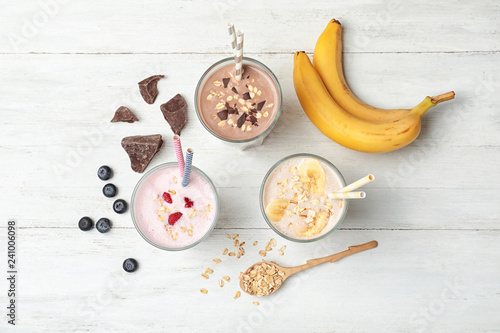 Flat lay composition with protein shakes and ingredients on wooden table