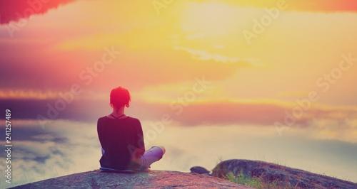 Fotografering Young woman sitting enjoying peaceful moment of beautiful colorful sunset
