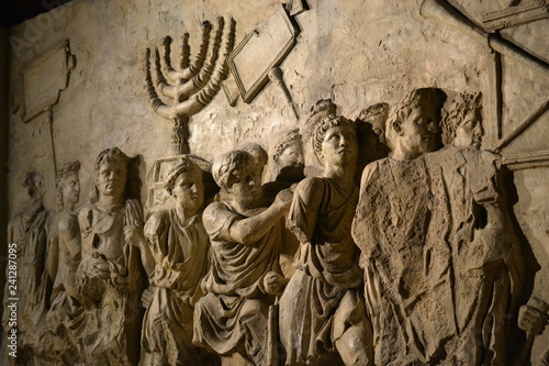 Fotografia Wall relief on arch of titus depicting Menorah taken from temple in Jerusalem in