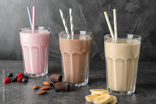 Glasses with different protein shakes and ingredients on table against grey background