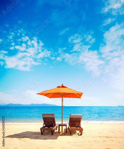 Fotografia Two lounge chairs with sun umbrella on a beach