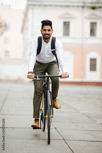 Fotografia, Obraz Indian Businessman riding bicycle to work on urban street in morning