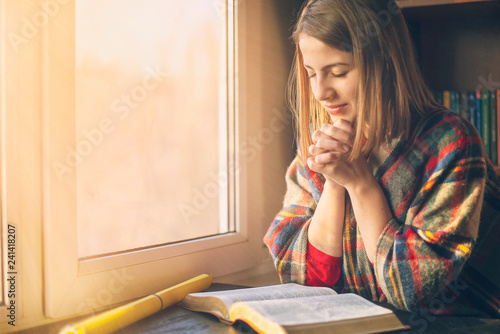 Beautiful woman praying having the Bible opened in front of he