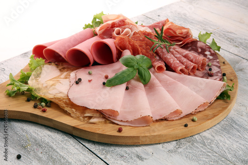 Food tray with delicious salami, pieces of sliced ham, sausage and salad. Meat platter with selection.