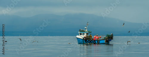 Valokuva Small Fishing Boat With Lobster Pods And Seagulls On Calm Atlantic In Front Of T
