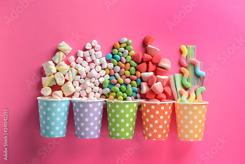 Paper cups with tasty candies on color background
