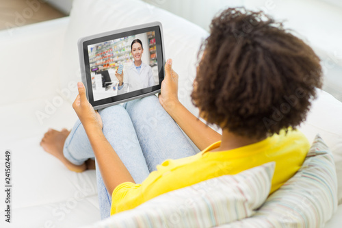 medicine, technology and healthcare concept - african american young woman having video chat with pharmacist on tablet pc computer at home
