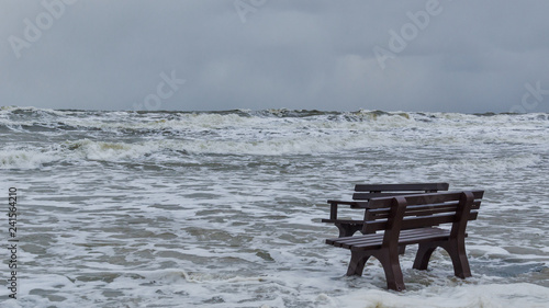 Photo STORM AT SEA - A bench flooded by storm waves on a sea beach in Kolobrzeg