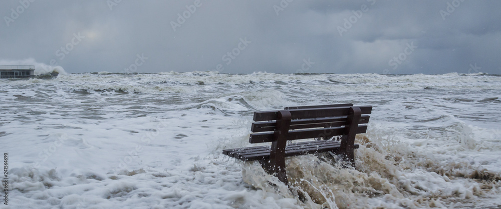 STORM AT SEA - A bench flooded by storm waves on a sea beach in Kolobrzeg