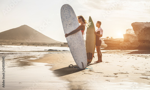 Surfers couple waiting for the high waves on beach