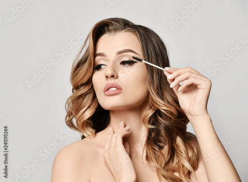 Beauty woman hold black mascara eyelashes  makeup brush clear healthy face portr Fototapeta