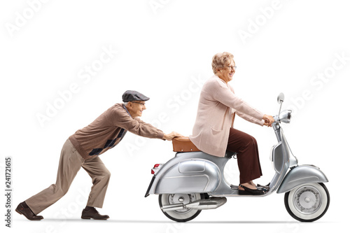 Senior man pushing a smiling senior woman riding a vintage scooter
