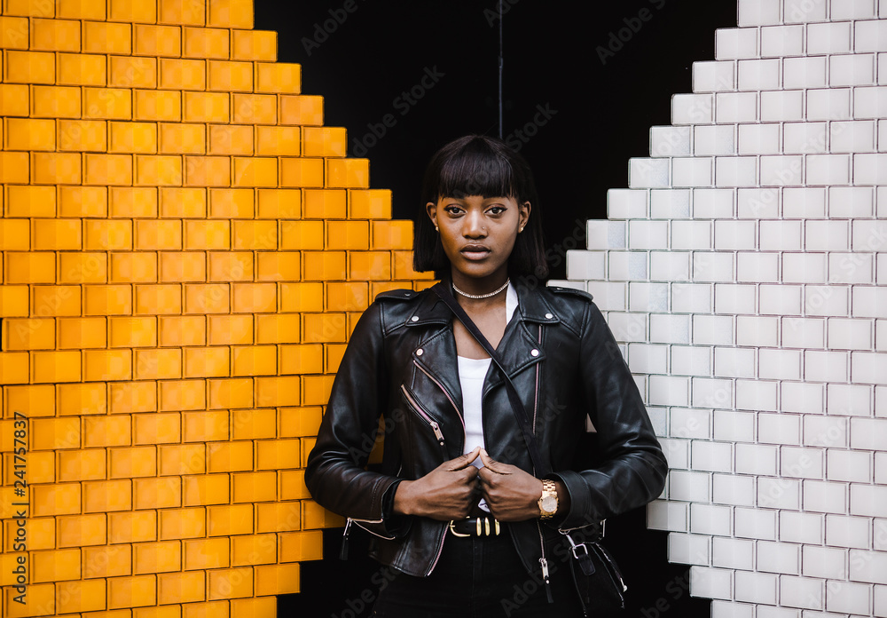 Portrait of a woman standing against wall