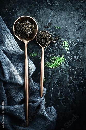 Black caviar in spoons on dark background. Natural sturgeon black caviar closeup. Delicatessen. Top view, flatlay