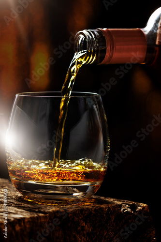 Pour whiskey out of the bottle in whiskey glass