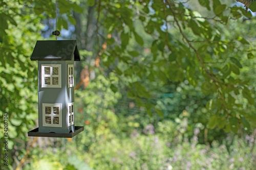 Cute birdhouse hanging in green garden concept Poster Mural XXL