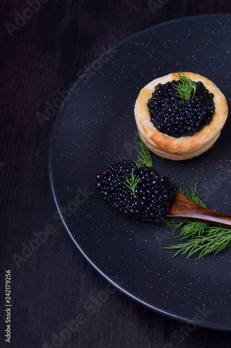 Black caviar in a wooden spoon and puff pastry tartlet on a dark plate