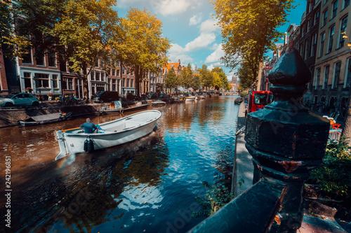 Fototapeta premium Kanał w Amsterdamie w jesiennym słońcu. Łódka pływająca wzdłuż drzewa, żywe odbicia, białe chmury na niebie. Holandia domy krajobraz punkt orientacyjny